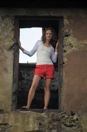 young woman in the window of a ruined house Stock Photo - 15383409