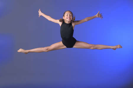 leg warmers: Gymnast girl jumping studio Stock Photo
