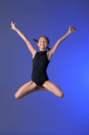 female gymnast: Gymnast girl jumping studio Stock Photo