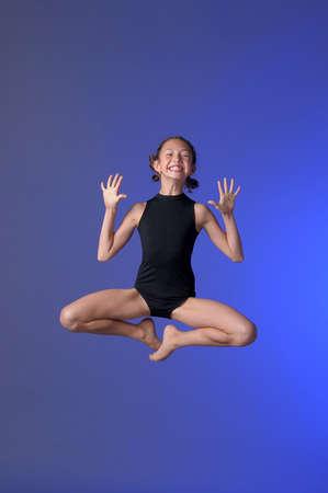 warmers: Gymnast girl jumping studio Stock Photo