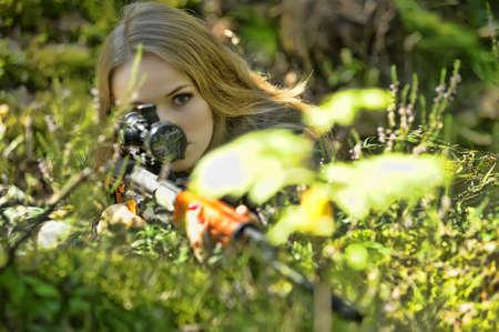 rubia joven con un rifle en sus manos