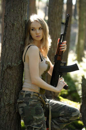young blonde with a rifle in his hands photo