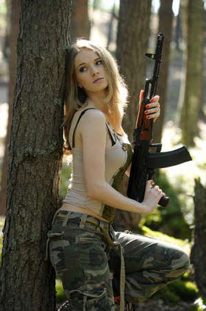 young blonde with a rifle in his hands
