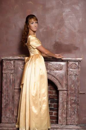 young woman in gold dress by the fireplace photo