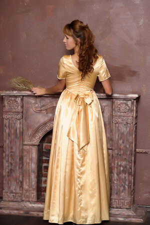 young woman in gold dress by the fireplace