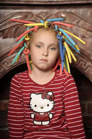Girl with multicolored hair curlers on her head photo
