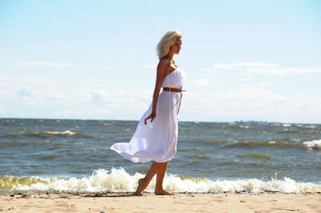 woman beach dress: girl in a white dress on the coast