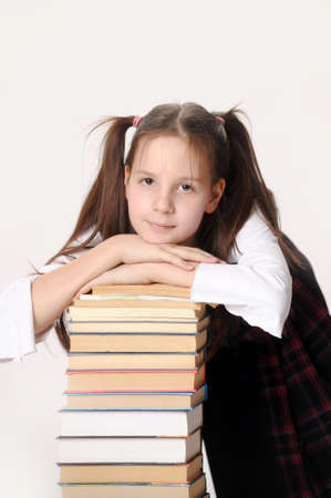 Cute little girl sit near a stack of books photo