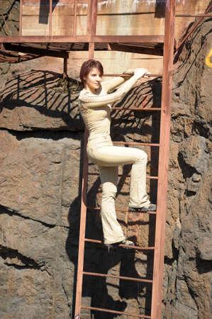 Woman climbing a ladder Stock Photo - 15428148