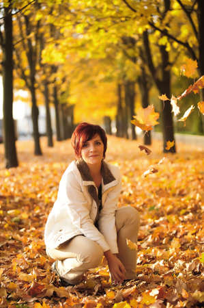 Girl in the park in autumn with yellow leaves photo