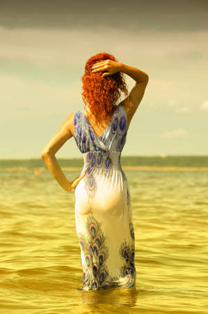 erotic fantasy: young woman in a dress in the water
