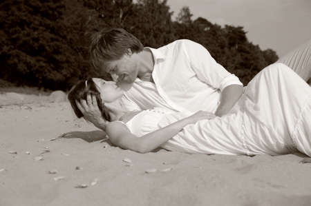 couple kissing while lying on the shore Stock Photo - 15412301