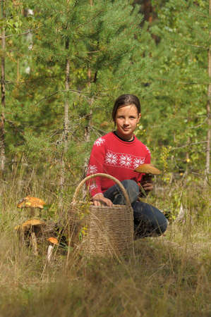 The girl the teenager with a basket and mushrooms