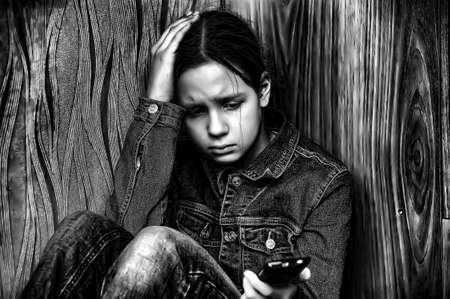 yeux tristes: La jeune fille surprise avec un t�l�phone mobile Banque d'images