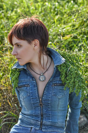 Young fashion model posing in jeans jacket photo