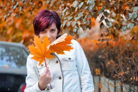 Young woman with autumn leaves in hand photo