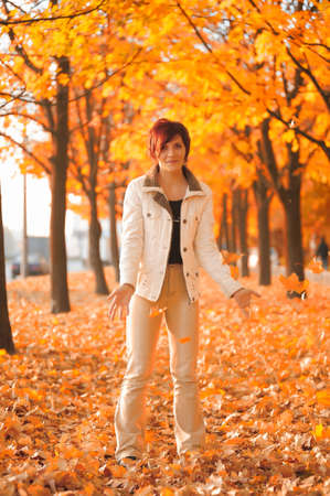 Girl throwing yellow maple leaves in autumn photo