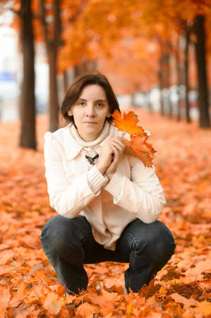 Woman with golden maple leaves photo