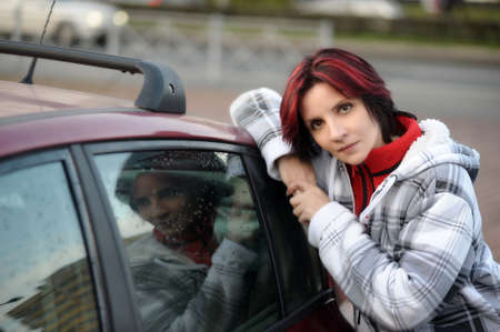 Pretty woman leans her elbows on a car  photo