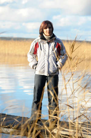 young woman in sports jacket near the lake in autumn photo
