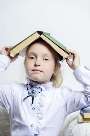 schoolgirl girl with a book on her head photo