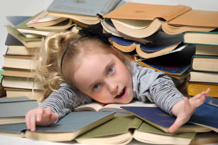 educations: girl schoolgirl littered with books Stock Photo