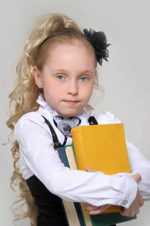 schoolgirl girl with a books in hands photo