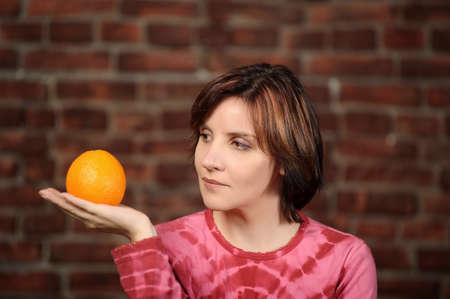 young woman with orange in hands photo