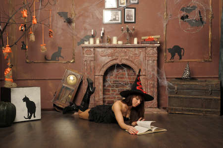 sexy devil: witch next to the fireplace Stock Photo