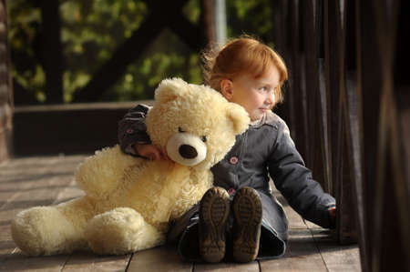 girl in coat with bear in hand photo