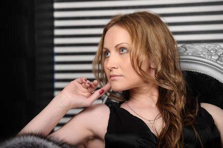 Femme assise sur le canapé de luxe millésime Banque d'images