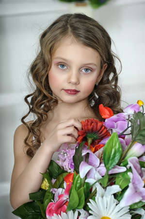 baby hairstyle: girl with a bouquet of flowers Stock Photo