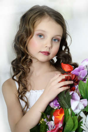 innocence: girl with a bouquet of flowers Stock Photo