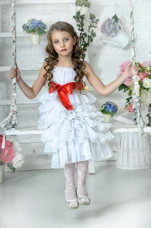 niña en un vestido blanco en un columpio