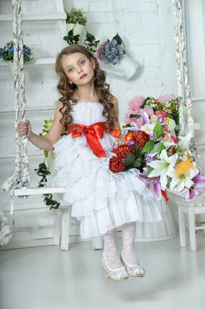 child girl nude: girl in a white dress on a swing with flowers Stock Photo