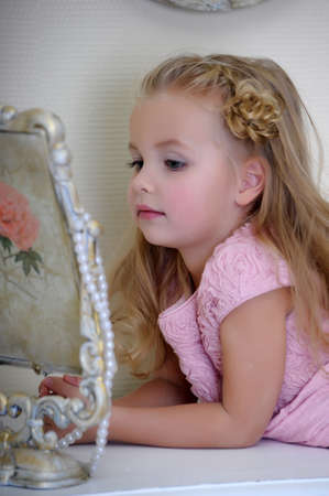 gypsy woman: Beautiful little girl looking to retro mirror