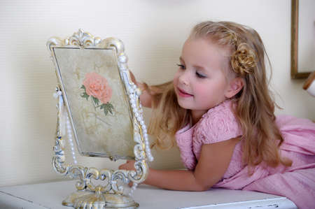 Beautiful little girl looking to retro mirror photo