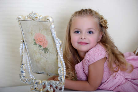 step daughter: Beautiful little girl looking to retro mirror