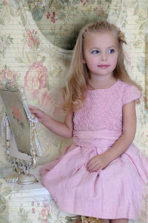 quiet baby: Beautiful little girl looking to retro mirror