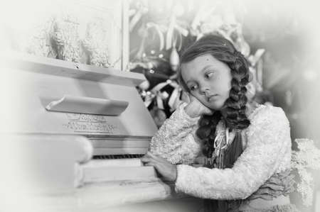 sad girl near the piano photo