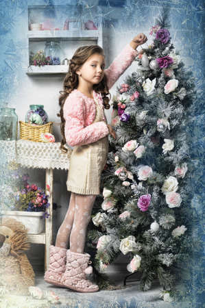 girl decorates the Christmas tree, in vintage style Stock Photo - 16889324