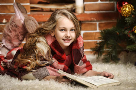 girl reading a book by the fireplace wrapped in a blanket