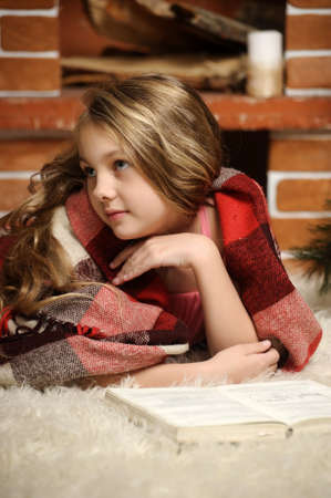 girl reading a book by the fireplace wrapped in a blanket photo