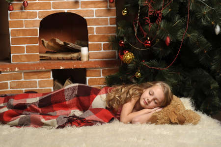 carpet on the floor: girl sleeping next Christmas tree