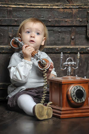 Portrait of little girl sitting with retro phone  Interior in retro style  photo