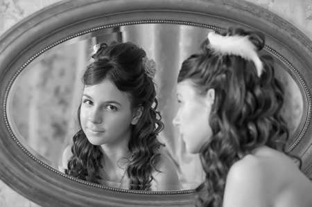 Beautiful young girl looking in the mirror  photo