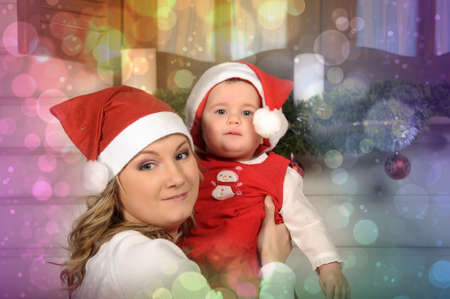 Christmas portrait of mother with her ​​little daughter in her arms photo