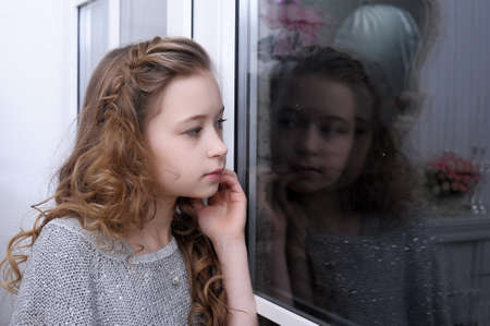 louvered: teen girl looking out the window Stock Photo