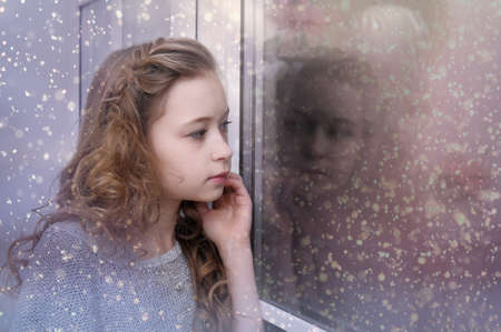 winter escape: teen girl looking out the window Stock Photo