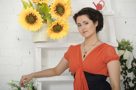 portrait of a young woman next to sunflowers photo